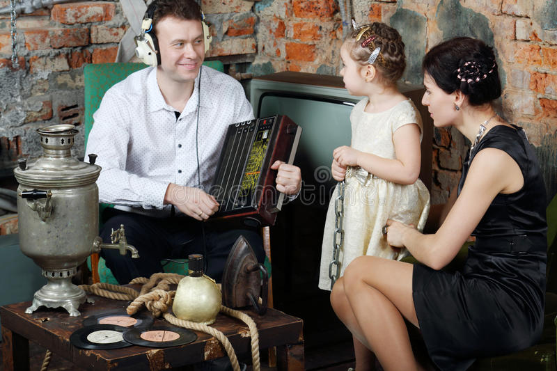 Father listens to old radio and mother with little daughter. Father in headphones listens to old radio and mother with little daughter look at him in very old royalty free stock images
