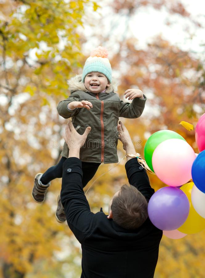 Father with little child. Happy father toss up little child with air-balloons, outing in autumn park stock images