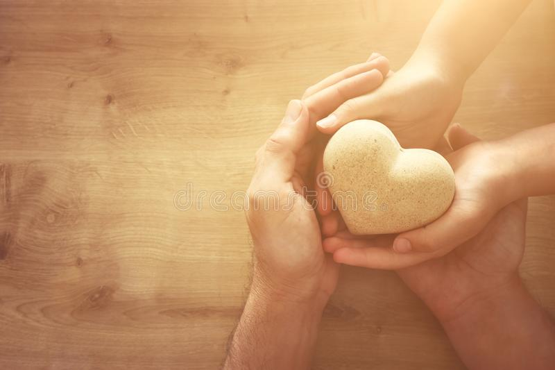 Father and little child holding together wooden heart. Happy father`s day concept stock photography