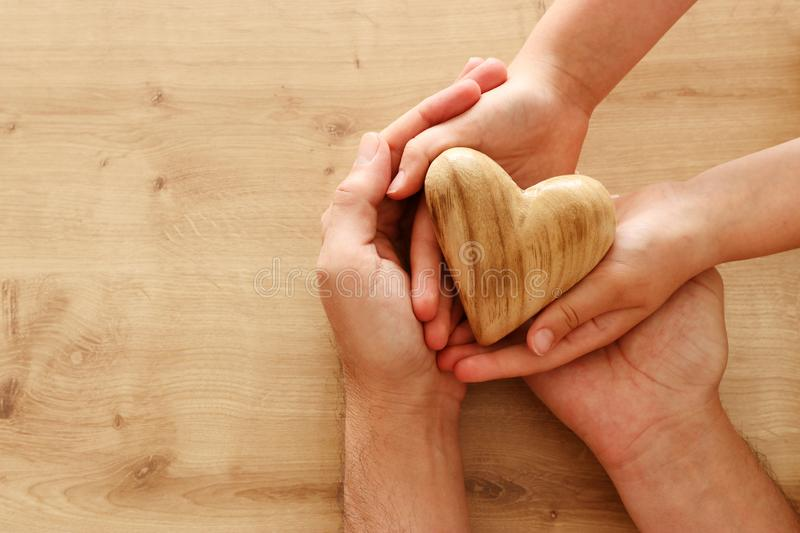 Father and little child holding together wooden heart. Happy father`s day concept royalty free stock images