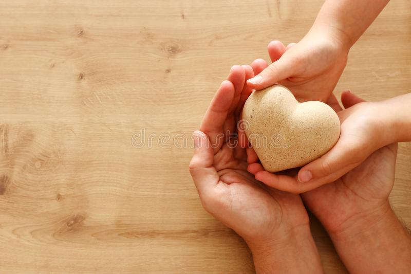 Father and little child holding together wooden heart. Happy father`s day concept.  royalty free stock photo