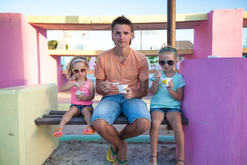 Father with little cute daughters eating ice-cream. Outdoor royalty free stock image
