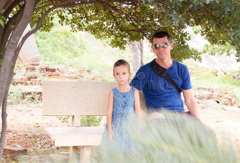 Father and little daughter enjoy view in a tree park, sitting on a bench. Children and dad together. Father and little daughter enjoy view in a tree park royalty free stock images