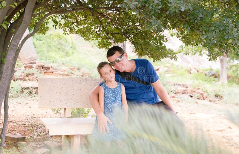 Father and little daughter enjoy view in a tree park, sitting on a bench. Children and dad together. Father and little daughter enjoy view in a tree park stock image