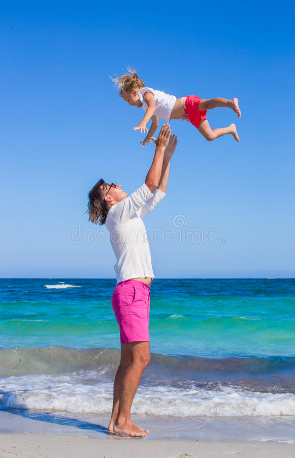Father and little daughter have fun during. Young father and his little daughter sitting on tropical white sand beach stock image