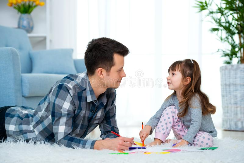 Father and little daughter having quality family time together at home. dad with girl lying on warm floor drawing with colorful. Felt tip pencils stock photos