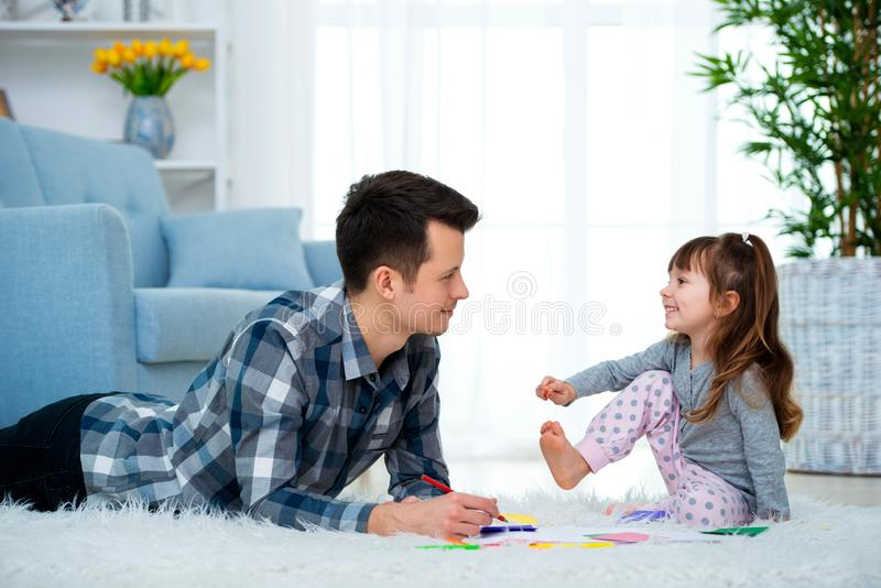Father and little daughter having quality family time together at home. dad with girl lying on warm floor drawing with colorful royalty free stock photos