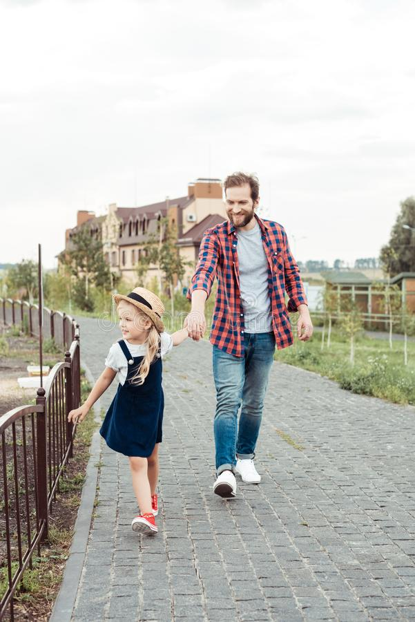 Father and little daughter holding hands while walking. In park together stock photo