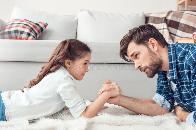 Father and little daughter at home lying on floor having arm wrestling competition smiling excited. Bearded men and little girl at home family time lying on stock photography