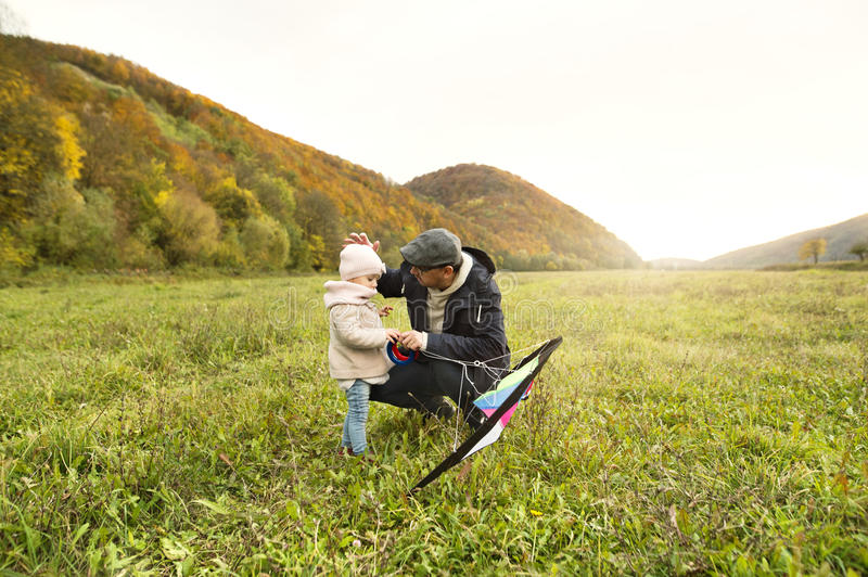 Father with little daughter with kite. Autumn nature. stock image