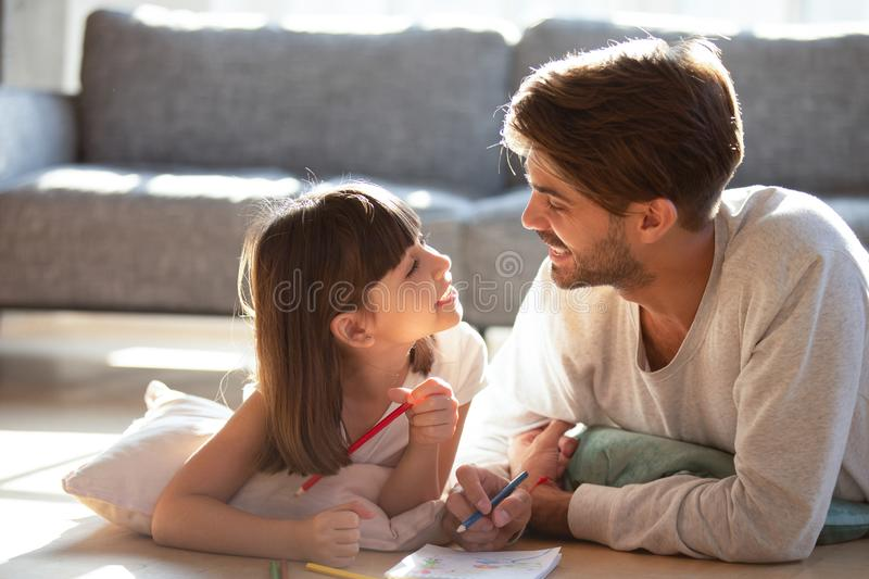 Father little daughter lying on floor drawing and talking stock images
