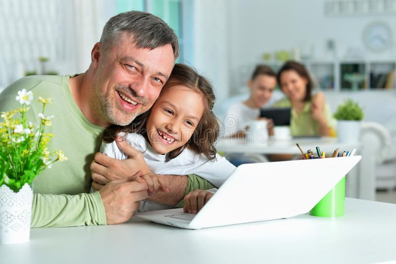 Portrait of father with little daughter using laptop stock image