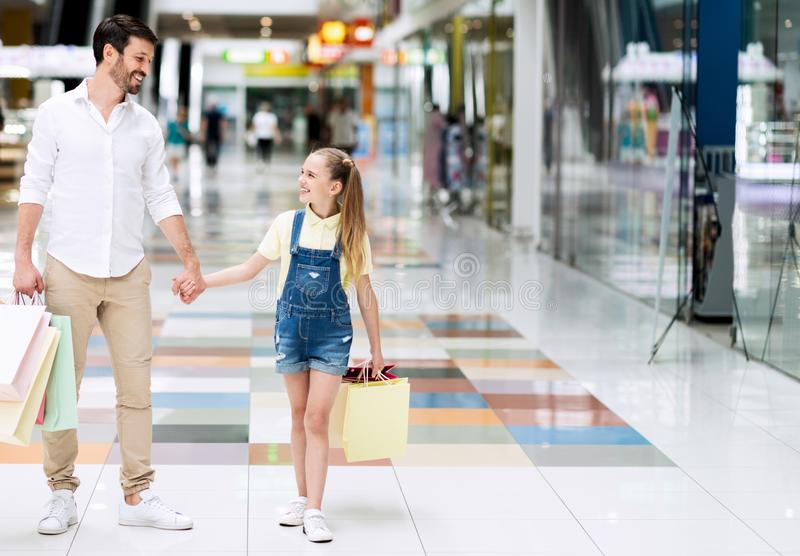 Father And Little Daughter Walking Carrying Shopping Bags In Hypermarket. Happy Father And Little Daughter Walking Holding Hands Carrying Colorful Shopping Bags stock image