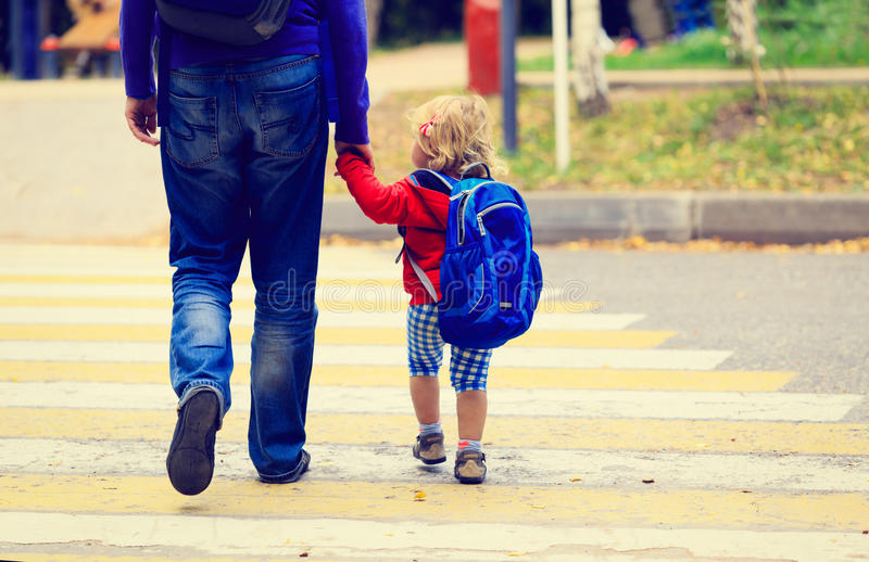 Father with little daughter walking to school or. Father walking little daughter with backpack to school or daycare royalty free stock photos