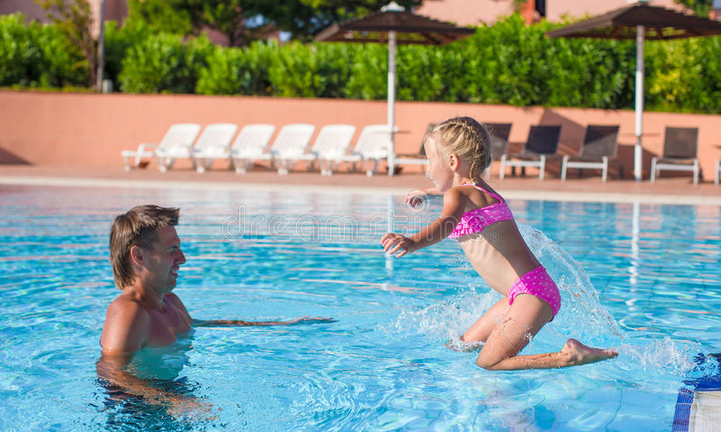 Father and little girl enjoy swimming in the pool. Cute little girl in the swimming pool looks at camera royalty free stock image