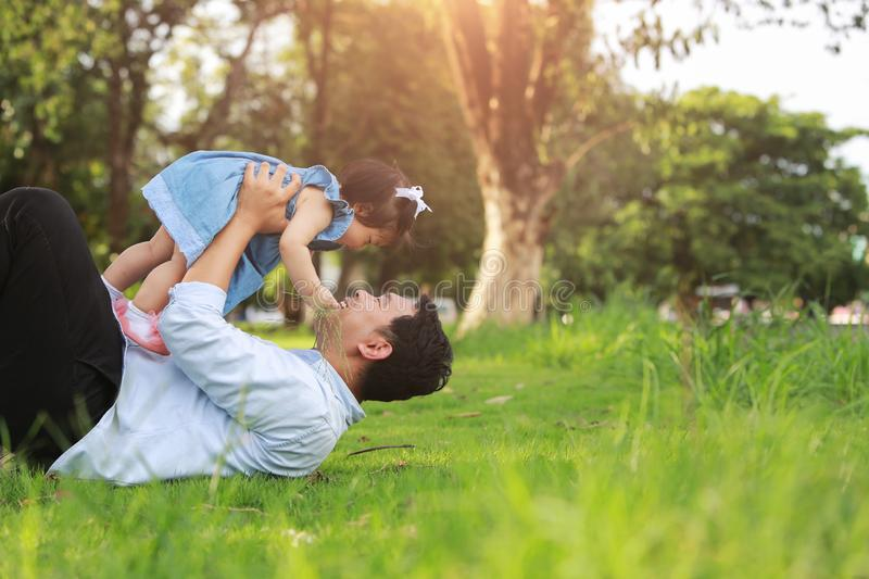 Father and little girl play lying on grass, low angle stock photos