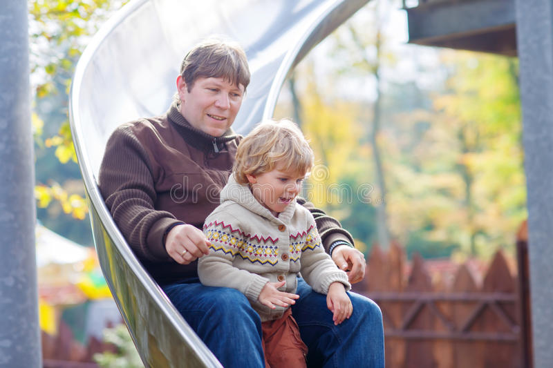 Father and little kid boy sliding on playground. Young dad and little son having fun on playground slide. Kid boy and men sliding together and laughing. Happy royalty free stock photo