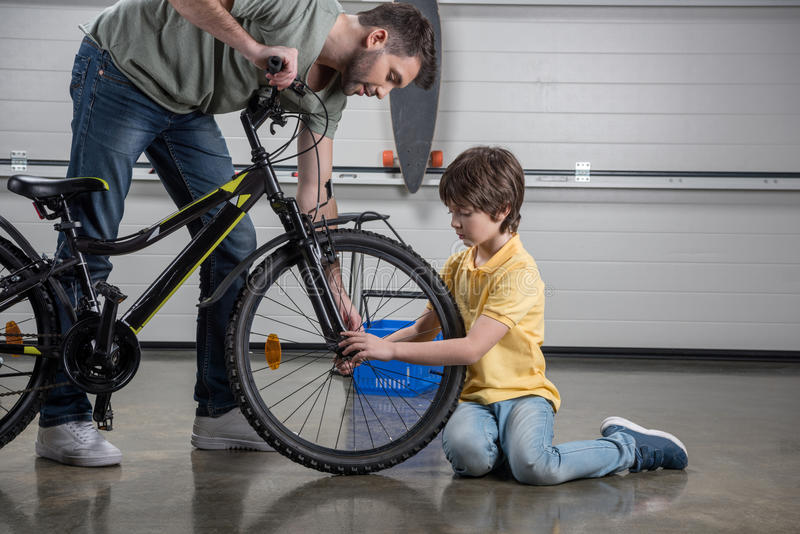 Father and little son checking tire of bicycle. Side view of father and little son checking tire of bicycle stock photo