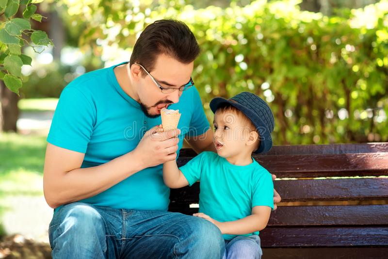 Father and little son eating ice-cream together in park in sunny summer or autumn day. Boy offers ice-cream to daddy. Happy family royalty free stock photo