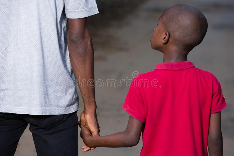 Father and little son holding hands walking on a road stock photo