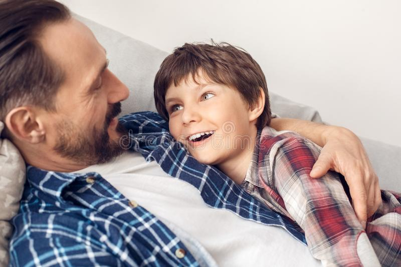 Father and little son at home lying on sofa boy looking at dad excited close-up. Father and little son together at home lying on sofa boy looking at dad smiling stock image