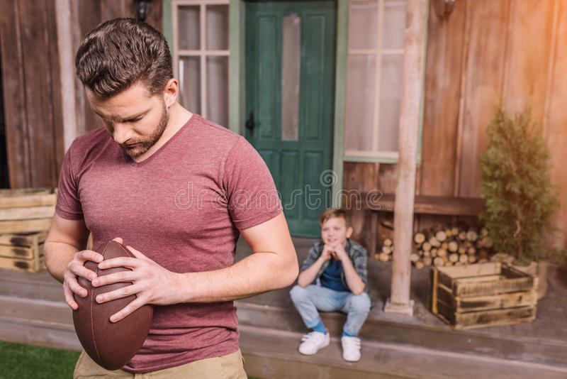 Father with little son playing american football with ball at backyard. Dad and son playing stock image