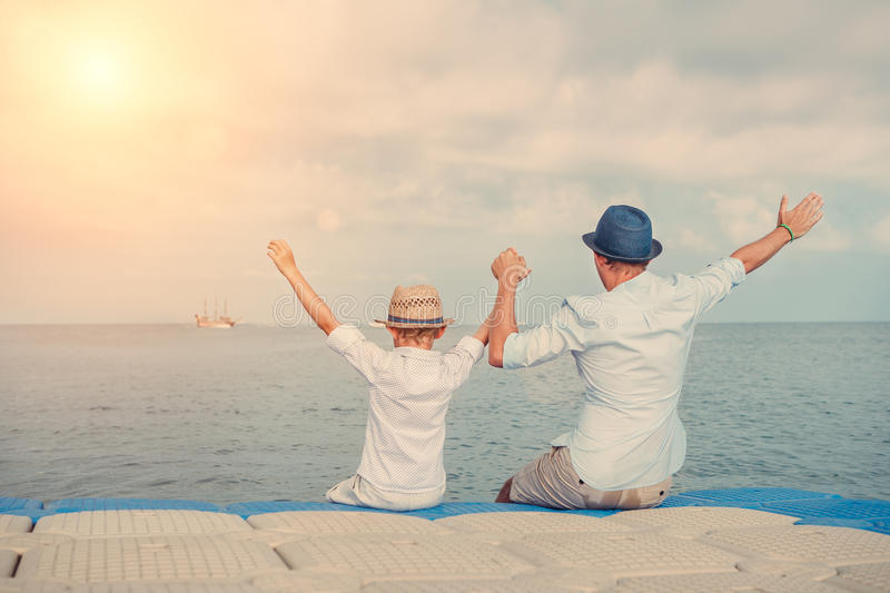 Father with little son salute a ship on the sea horizon line royalty free stock photo