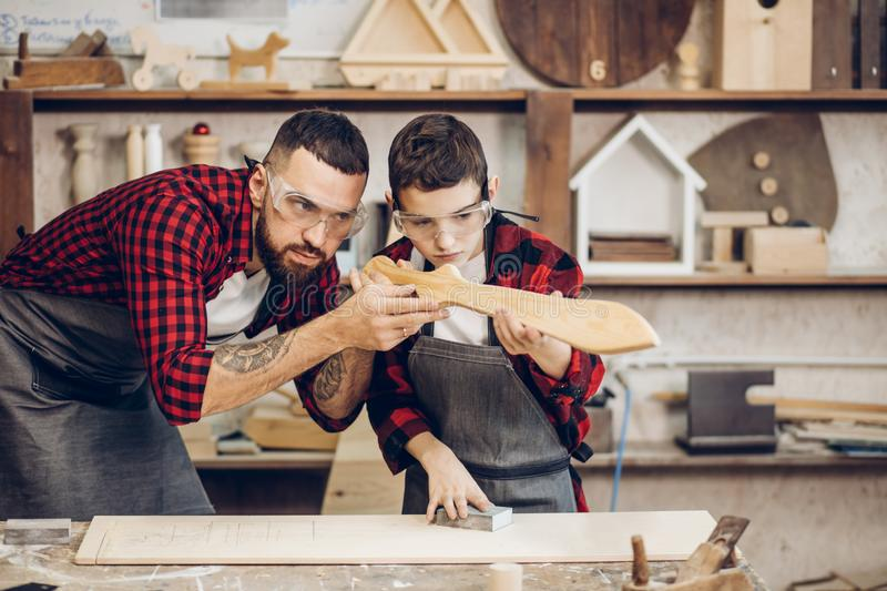 Father and little son testing hand-made wood sward evenness at workshop stock photos