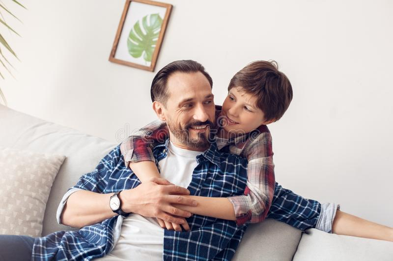 Father and little son at home boy hugging dad sitting on sofa looking at each other joyful. Father and little son together at home boy hugging dad sitting on stock photography