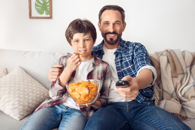 Father and little son at home sitting on sofa boy eating chip watching tv concentrated dad switching channels joyful stock images