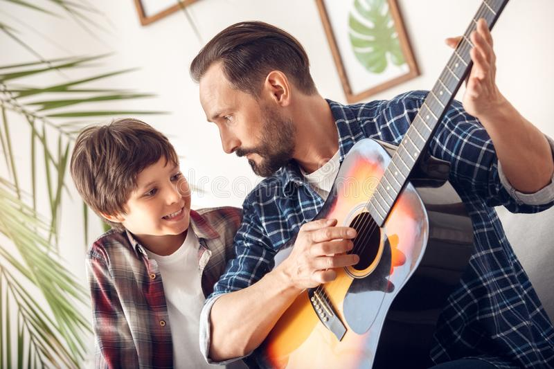 Father and little son at home sitting on sofa boy smiling looking at dad playing guitar. Father and little son together at home sitting on sofa boy smiling stock images