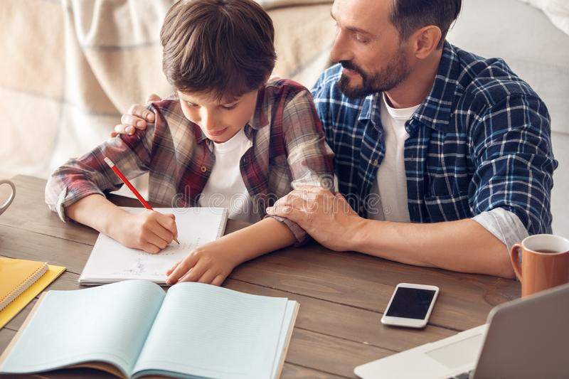 Father and son at home sitting at table dad hugging boy writing homework smiling happy close-up royalty free stock image
