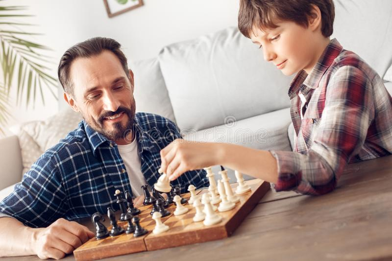Father and little son at home sitting at table playing chess dad looking ceerful at boy holding knight thoughtful stock photography