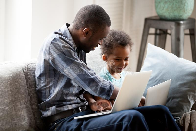 Father with little son using computers sitting on couch royalty free stock photo