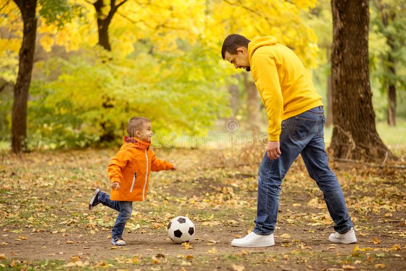 Dad and son having fun outdoors: little boy playing soccer with father in autumn park royalty free stock photo