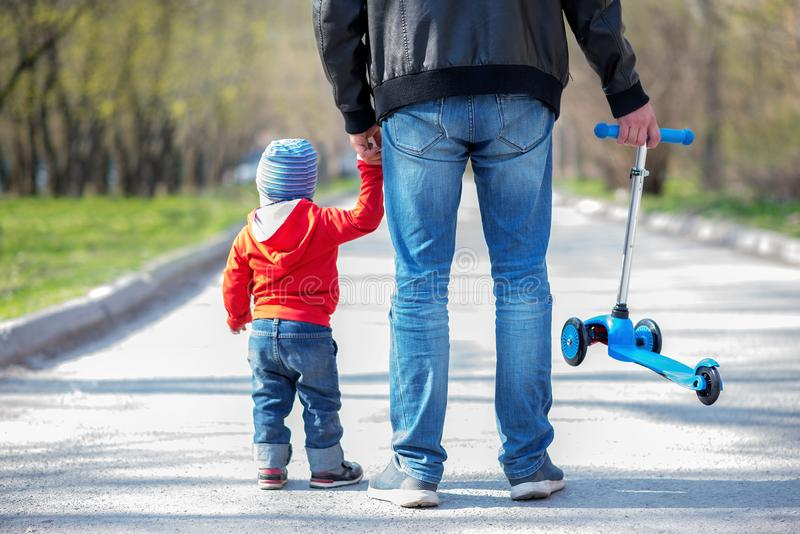 Father and little toddler son on a spring walk with a blue kick scooter. Kid is holding hand of father. Active family on a walk stock photography
