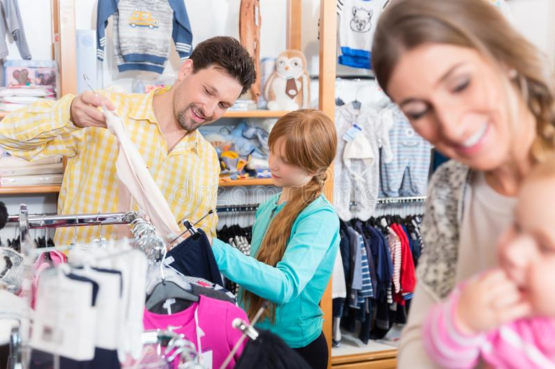 Father looking clothes for her daughter in shop. Father looking clothes on rail for her daughter in shop royalty free stock photography