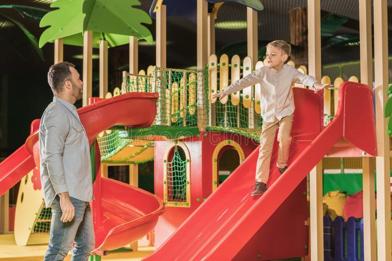 father looking at cute little son playing on slide royalty free stock image
