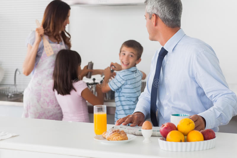 Father looking at his family cooking in the kitchen. In the morning before work stock photo