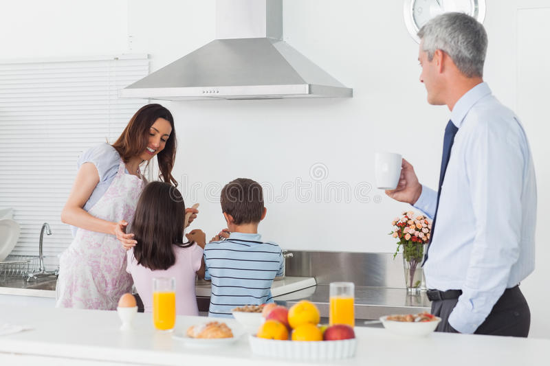 Father looking at his family cooking in the kitchen. Before work in the morning stock images