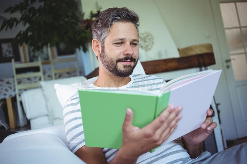 Father looking at photo album in living room stock photography