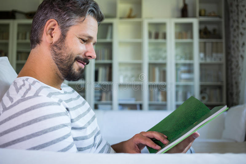 Father looking at photo album in living room stock photos