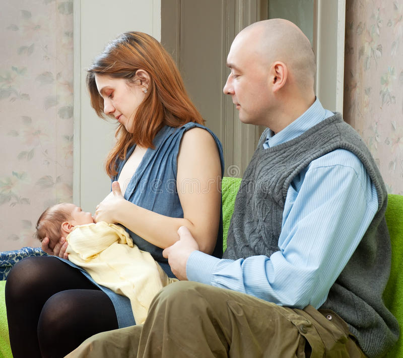 Father looks at the baby sucking breast of mother royalty free stock photos