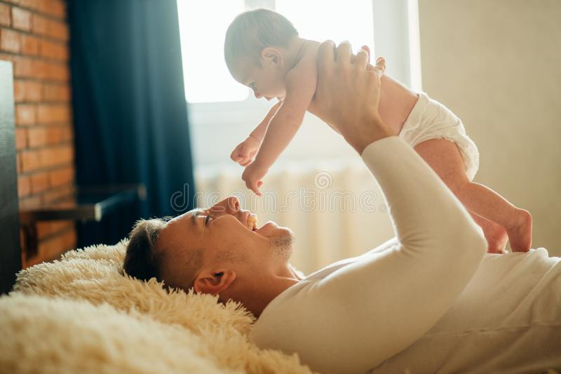 Father lying with cute baby daughter on bed royalty free stock photography