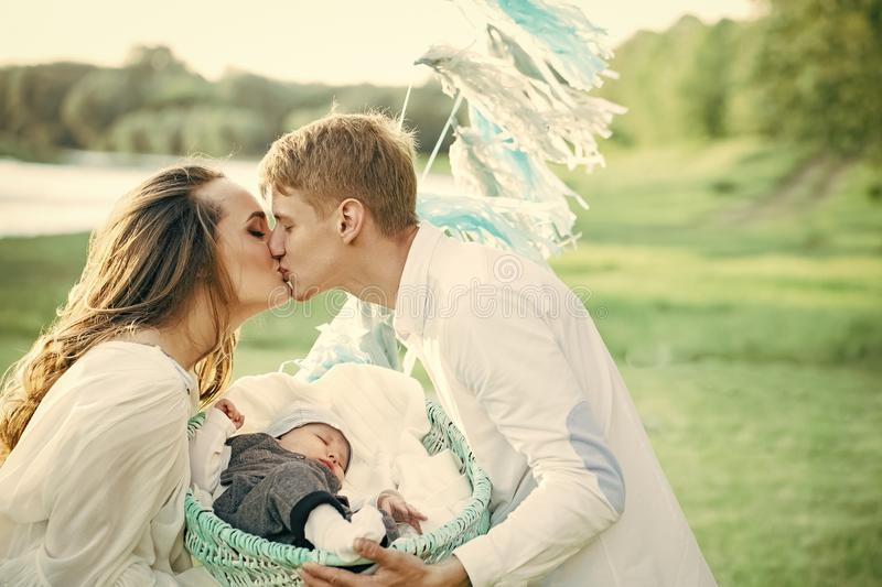 Father man kiss mother woman with baby child in crib. Father men kiss mother women with baby child in crib on natural landscape. Family, love, care, trust stock images