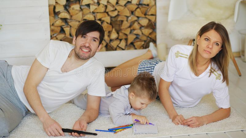 Father man mother watch TV while their son draw picture in their living room. Father men mother watch TV while their son draw picture in their living room at stock image