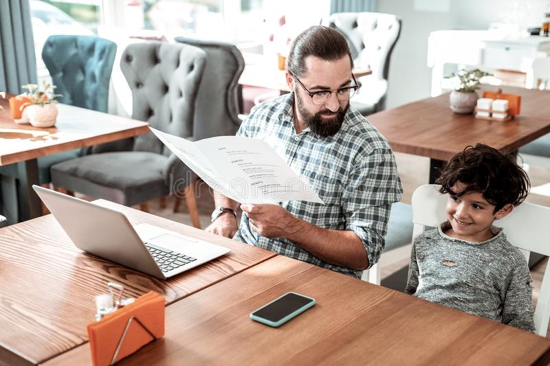 Bearded father wearing glasses holding menu coming to restaurant with son stock photo