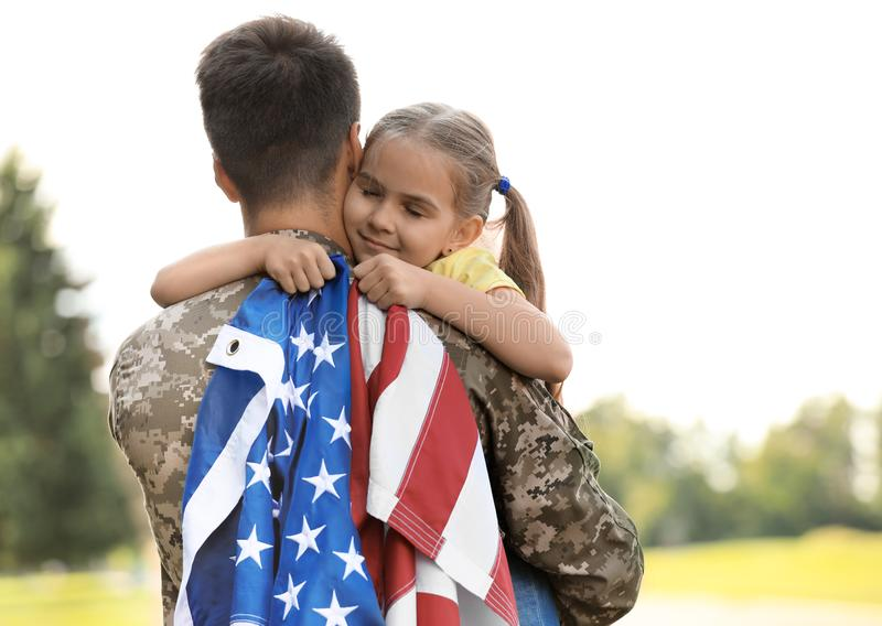 Father in military uniform with American flag and his daughter at park royalty free stock photo