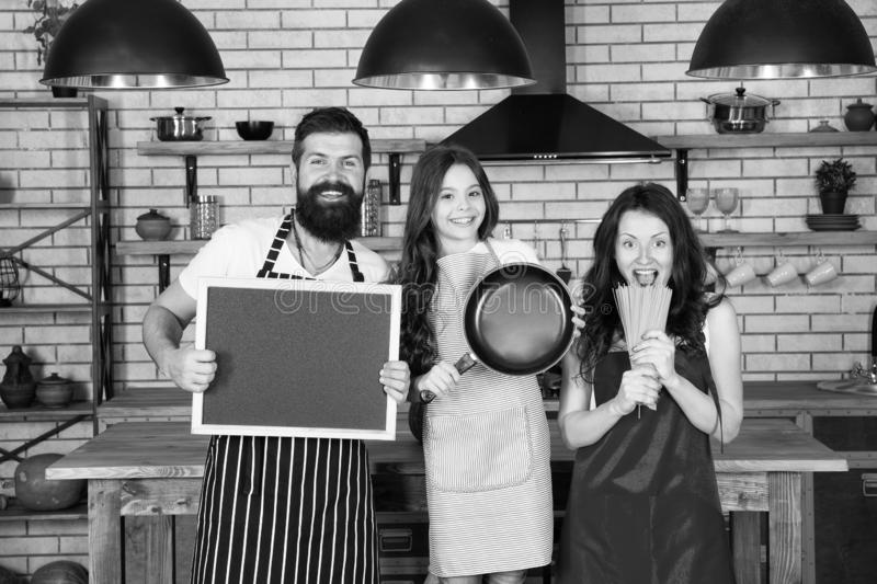 Father, mother and child cooking. Mother father with little girl. Family day. Happy family in kitchen. Little girl with. Parents in apron. Bearded men with royalty free stock photo