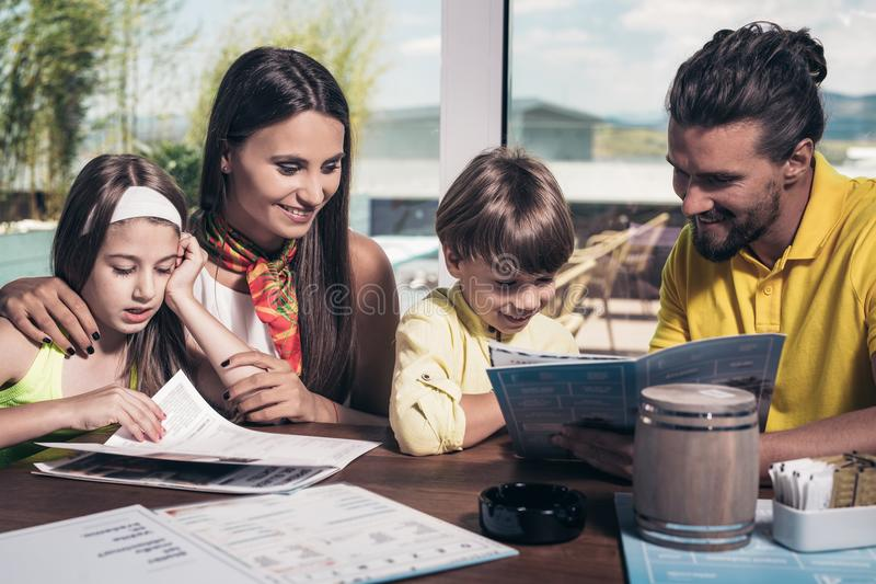 Father and mother with children enjoying meal in restaurant. stock photo